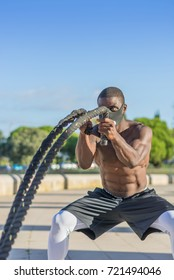male muscular training with battle ropes and training mask in a park outdoor