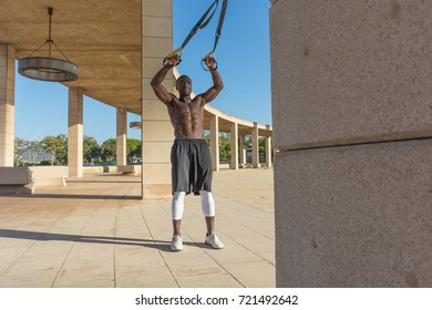 male muscular training with system trx in a park outdoor
