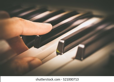 male musician fingers playing on piano keys, shallow dept of field. focus on forefinger. music background