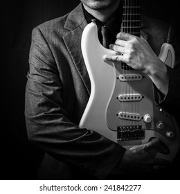 male musician in grey suit holding electric guitar on dark background
