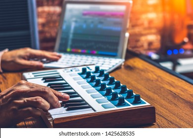 male musician hands arranging a song on midi keyboard and laptop computer. music technology concept