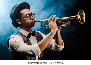 male musician in hat and eyeglasses playing on trumpet on stage with dramatic lighting and smoke