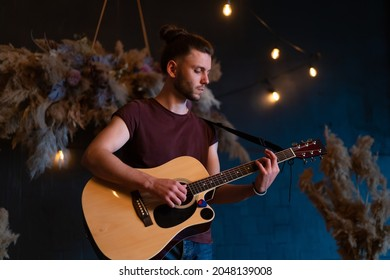 Male musician playing acoustic guitar. Guitarist plays classical guitar on stage in concert Handsome young hipster male guitar player perform private party Stylish long hair Medium shoot