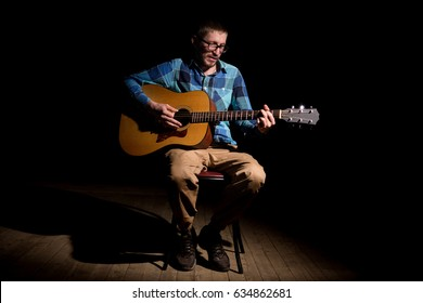 Male musician playing acoustic guitar and singing.