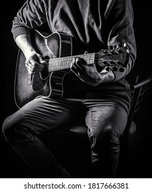 Male musician playing guitar, music instrument. Man's hands playing acoustic guitar, close up. Acoustic guitars playing. Music festival.
