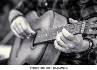 Male musician playing guitar, music instrument. Man's hands playing acoustic guitar, close up. Acoustic guitars playing. Music concept. Guitars acoustic. Live music. Music festival. Black and white.