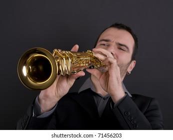 male musician playing strait soprano saxophone