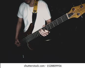 A male musician plays an electric bass instrument with a pick on the stage with focus on hand.