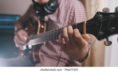 Male musician plays the guitar, hands close up