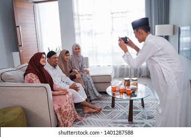 male muslim taking picture of his family while sitting on a couch at home in eid mubarak