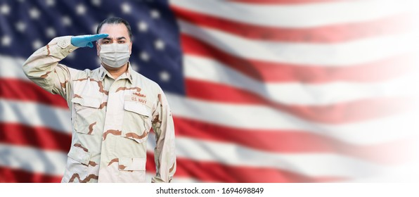 Male Navy Medical Personel Saluting Wearing Personnel Protective Exquipment (PPE) With American Flag Background Banner.