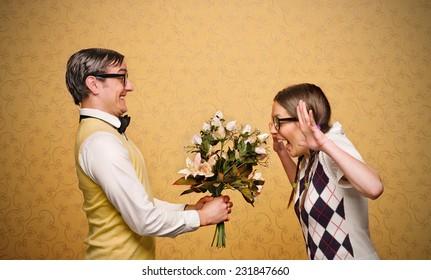 Male nerd giving flowers to female nerd
