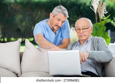 Male nurse explaining something on laptop to senior man at nursing home porch