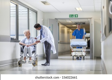 Male nurse pushing stretcher gurney bed in hospital corridor with doctor & senior female patient