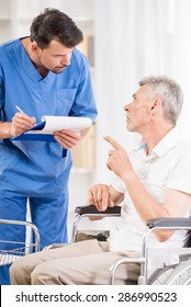 Male nurse taking care about senior patient in wheelchair.