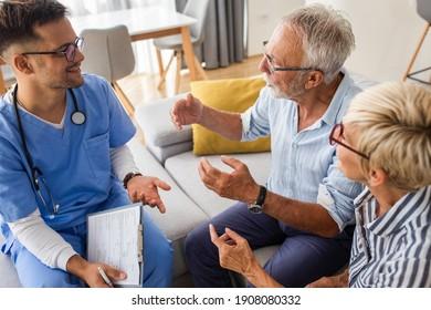 Männliche Krankenschwester, die mit älteren Patienten während eines Hausbesuchs spricht.