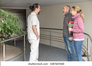 male nurse with two visitors in a corridor of a hospital or retirement home
