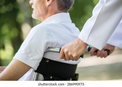 Male nurse walking with senior patient in wheelchair in garden near hospital. Close-up.
