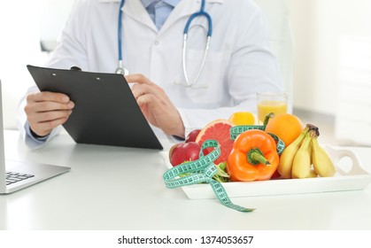 Male nutritionist working in his office