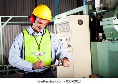 male occupational health and safety officer inside factory doing inspection