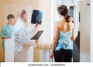 Male octor Standing Assisting Female Patient Undergoing Mammogram X-ray Tes. Man oncologist talking with her patient on mammography examination.