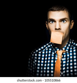 Male Office Administration Clerk Impersonating A Notice Board With Blank Orange Sticky Note On Face In A Copy Space Conceptual On Black Background