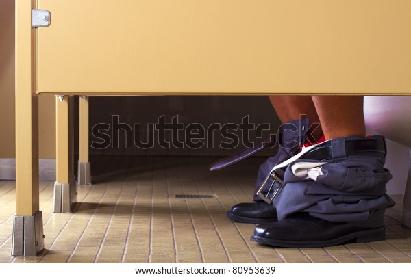 male office worker in a bathroom stall