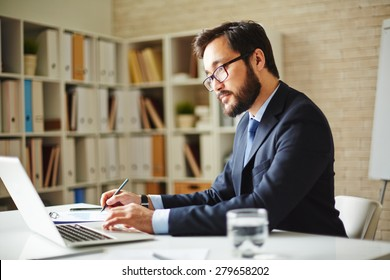 Male office worker browsing in laptop for necessary information