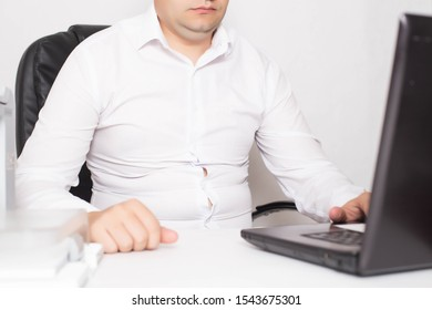 Male office worker with double chin and obesity at a laptop. The concept of malnutrition and sedentary lifestyles