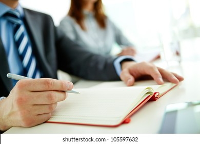 Male office worker making appointments and notes in his organizer