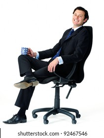 Male office worker relaxes on a chair, enjoying a cup of coffee