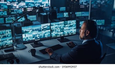 Funcionario masculino trabaja en una computadora con video CCTV de vigilancia en un centro de monitoreo de puerto con múltiples cámaras en una gran pantalla digital. Empleados sentados frente a pantallas con grandes datos.