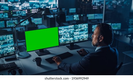 Male Officer Works on a Computer with Surveillance CCTV Video and Green Mock-up Chroma Key in a Harbour Monitoring Center with Multiple Cameras. Employees Sit in Front of Displays with Big Data.