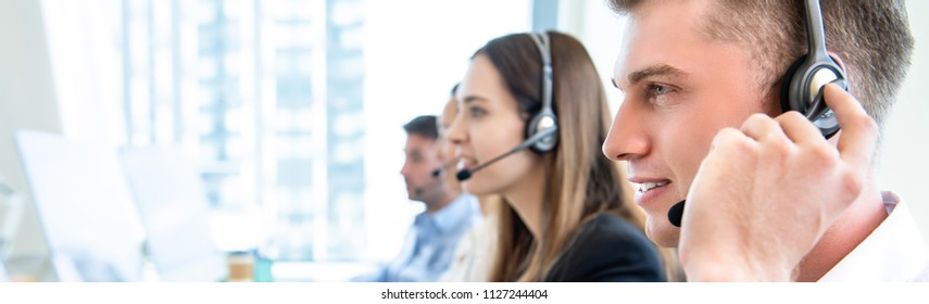 Male operator staff with team talking to customers in call center office, panoramic web banner with copy space