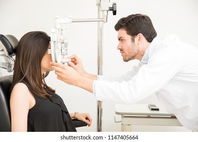 Male ophthalmologist adjusting panel of phoropter while examining female patient eyes
