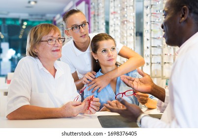 Male optician helping clients to choose a spectacles  in medical shop