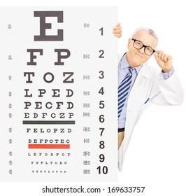 Male optician standing behind eyesight test, isolated on white background, shot with a tilt and shift lens