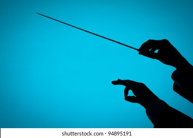 Male orchestra conductor hands, one with baton. Silhouette against blue background.