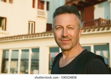 Male outdoor street portrait. Mid adult man walking at summer city Saint Jean de Luz streets, France.