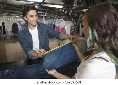Male owner showing jeans measurement to female client in laundry
