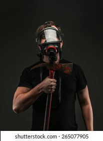 Male in oxygen mask holds axe. Isolated on grey