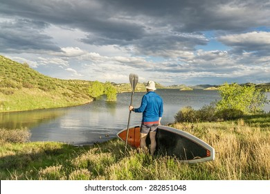 male paddler with stand up paddleboard (SUP) on a grassy shore of mountain lake - Horsetooth Reservoir near Fort Collins, Colorado