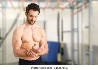 Male with pain in his wrist, isolated in a gym