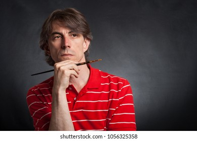 Male painter with brush in hand dreams.