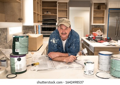 Male painter looking at camera holding wet paintbrush in messy home kitchen, fixer upper remodeling project, empty paint cans stacked on kitchen counter, lids off