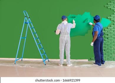 Male painters doing repair in room