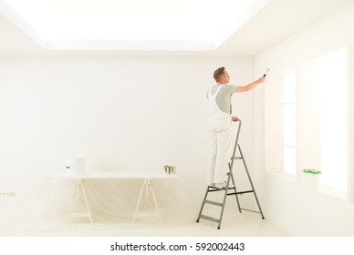 male painting his white home walls from a stepladder
