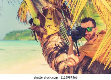 Male Paparazzi hides behind a tree on a tropical beach to take pictures of a hidden camera