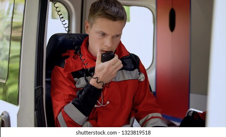 Male paramedic talking by radio, sitting in ambulance, ready to drive on call