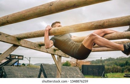 Male participant in a obstacle course doing weaver obstacle